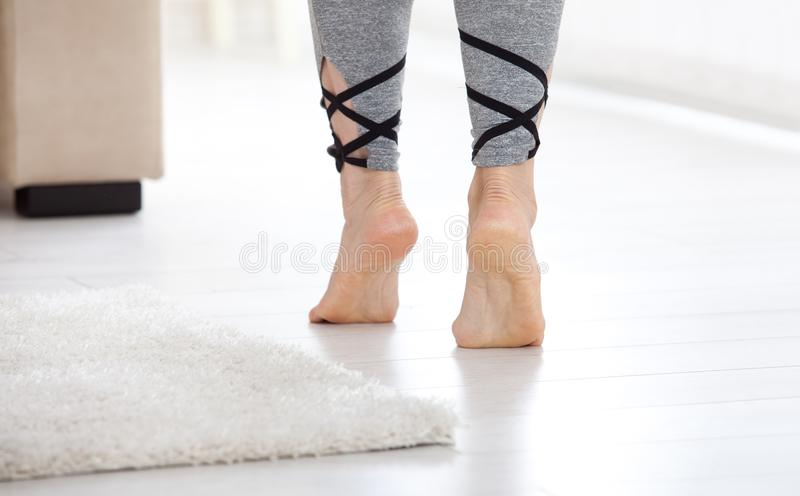 Warm floor concept. Closeup of female legs stepping by hardwood floor at home. Warm floor concept. Close-up of female legs stepping by hardwood floor at home royalty free stock image