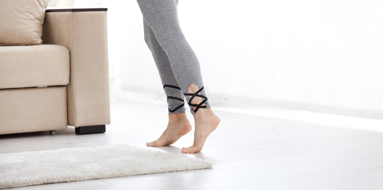 Warm floor concept. Closeup of female legs stepping by hardwood floor at home. Warm floor concept. Close-up of female legs stepping by hardwood floor at home stock image
