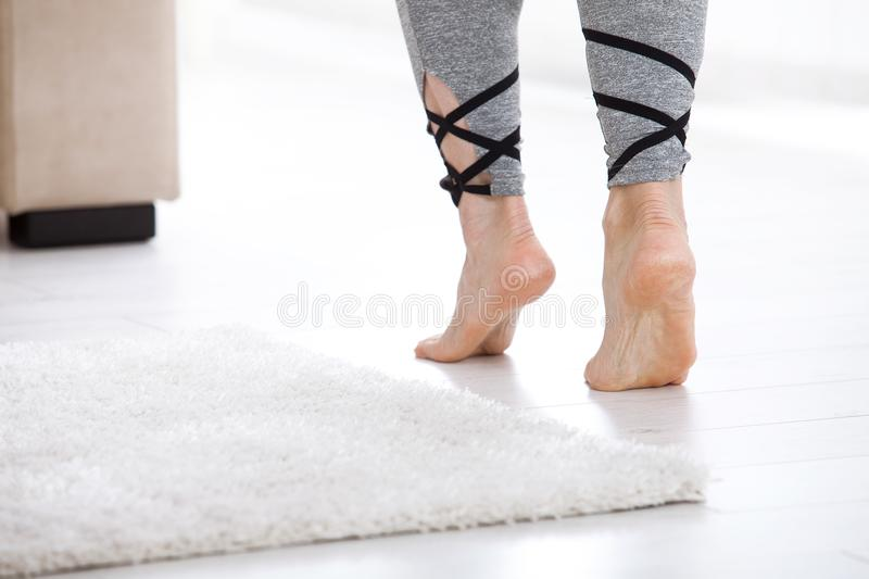 Warm floor concept. Closeup of female legs stepping by hardwood floor at home. Warm floor concept. Close-up of female legs stepping by hardwood floor at home royalty free stock images