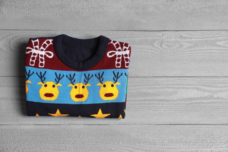 Warm folded Christmas sweater on grey  table, top view. Space for text. Warm folded Christmas sweater on grey wooden table, top view. Space for text stock photo