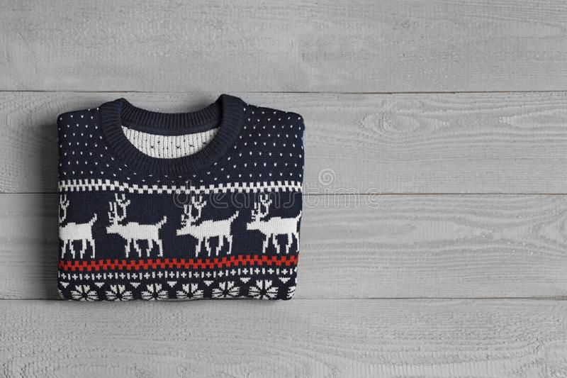 Warm folded  sweater on grey wooden table, top view. Space for text. Warm folded Christmas sweater on grey wooden table, top view. Space for text royalty free stock images