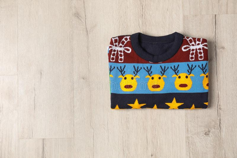 Warm folded Christmas sweater on light wooden table. Space for text. Warm folded Christmas sweater on light wooden table, top view. Space for text stock photography