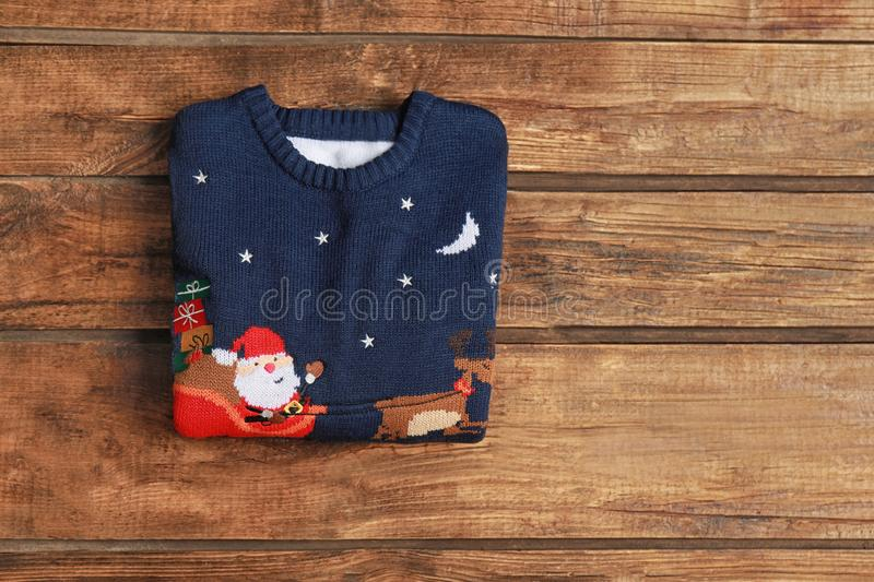 Warm folded Christmas sweater on wooden , top view. Space for text. Warm folded Christmas sweater on wooden table, top view. Space for text stock image