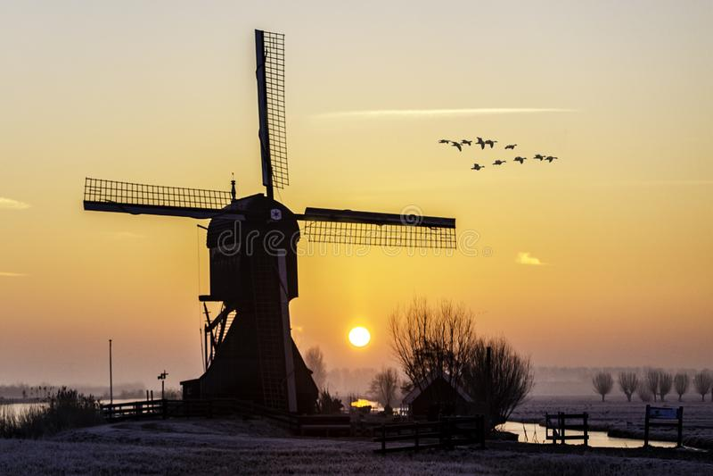 Warm and frozen windmill sunrise stock photo
