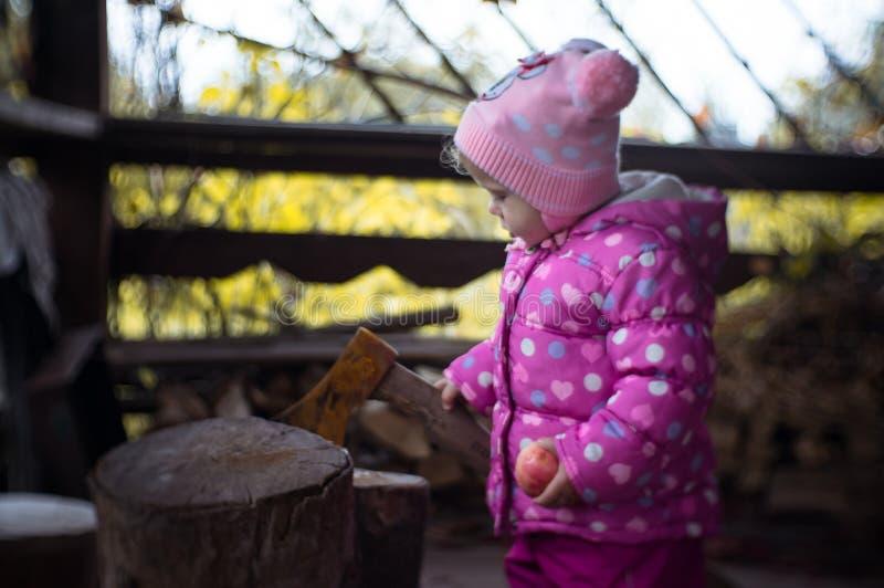 Warm gekleidetes kleines Mädchen auf dem Hintergrund der alten Axt stockfotografie