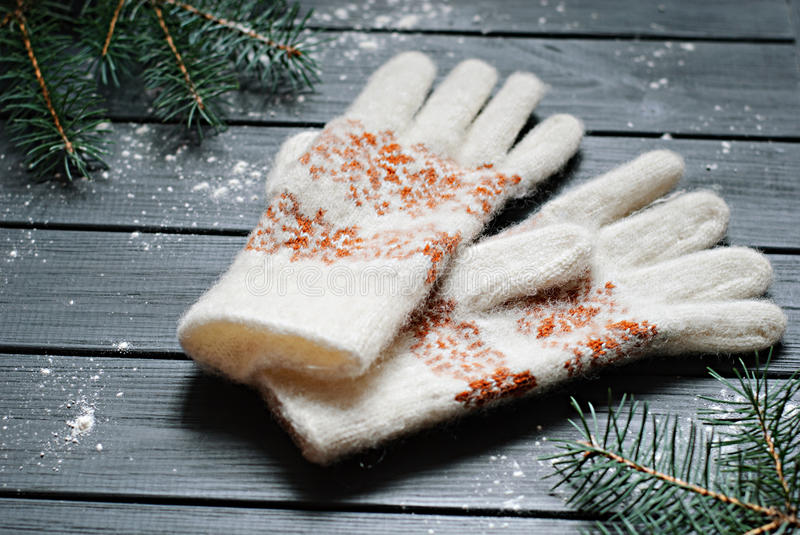Warm gloves or mittens with fir branches on wooden background royalty free stock image