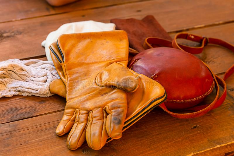 Warm gloves from vintage leather light brown and orange for hunting for traditional large round jars stock images