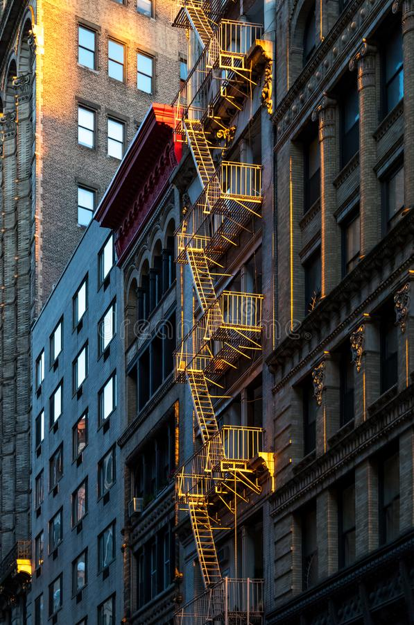 Warm glow of sunlight shining on a fire escape on the front of a. N old building in New York City stock images