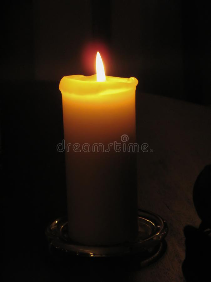 Warm Golden Light from Glowing Church Candle. With dark background stock photo