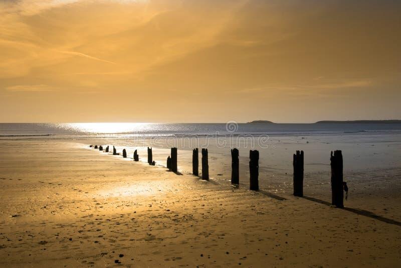 Warm golden sunrise over the beach breakers stock image