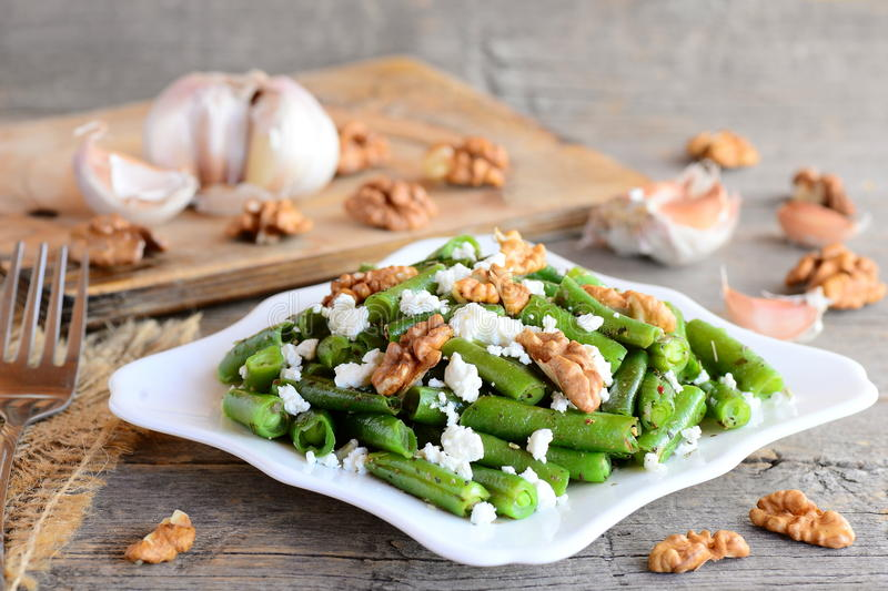 Warm green bean salad with cottage cheese and peeled walnuts. Diet green beans recipe. Vegetarian main dish. Rustic style. Green beans photo. Green string bean stock photos