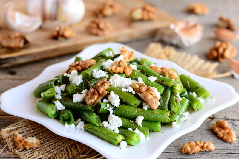 Warm green beans salad with cottage cheese and walnuts on a white plate and old wooden table. Rustic style. Easy green beans stock image