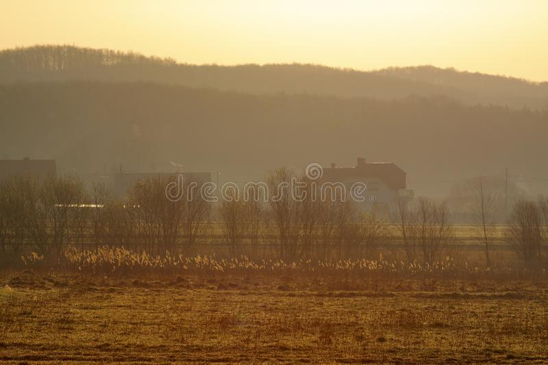 Warm hazy sunrise over village stock image