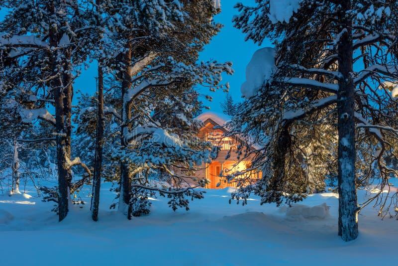 Warm huis in het sneeuwbos van de nachtwinter stock afbeeldingen