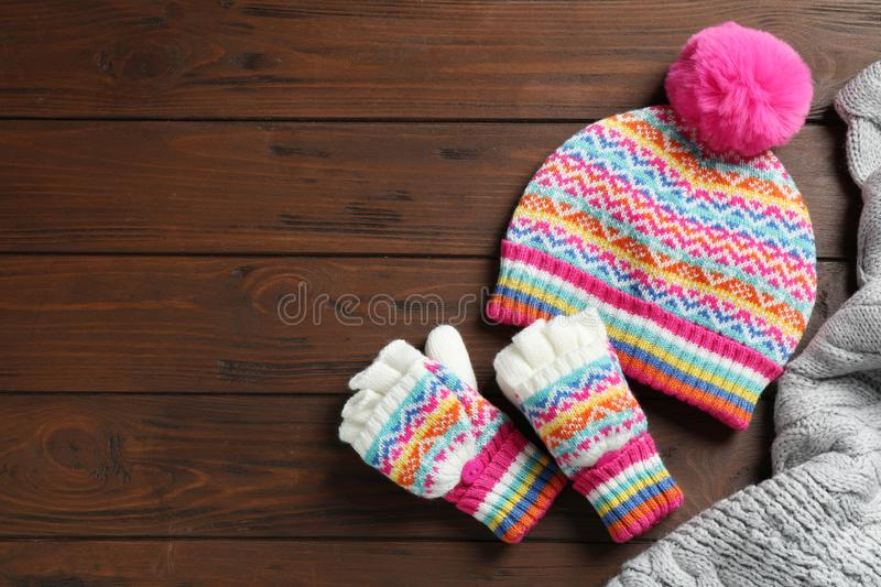 Warm knitted clothes on wooden background. Space for text. Warm knitted clothes on wooden background, flat lay. Space for text stock photos