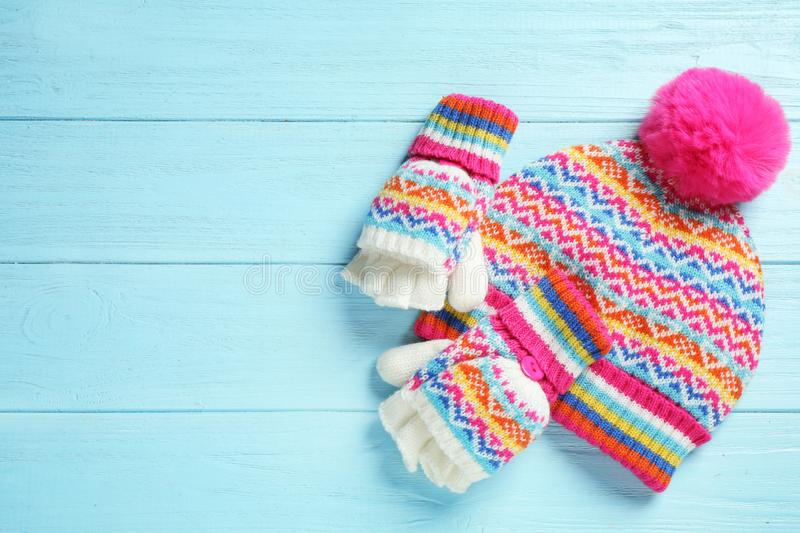 Warm knitted hat and mittens on blue wooden background. Space for text. Warm knitted hat and mittens on blue wooden background, flat lay. Space for text stock image