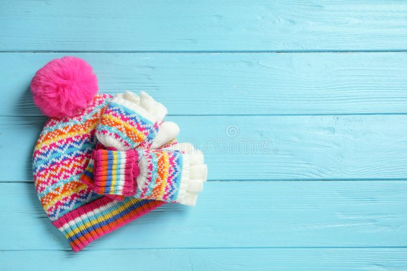 Warm knitted hat and mittens on blue wooden background. Space for text. Warm knitted hat and mittens on blue wooden background, flat lay. Space for text stock photo
