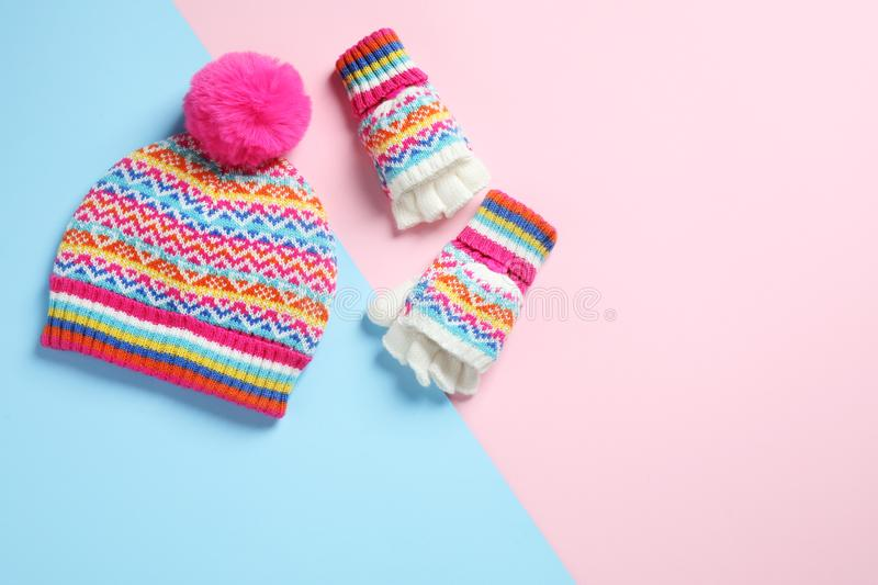Warm knitted hat and mittens on color background. Space for text. Warm knitted hat and mittens on color background, flat lay. Space for text royalty free stock photography