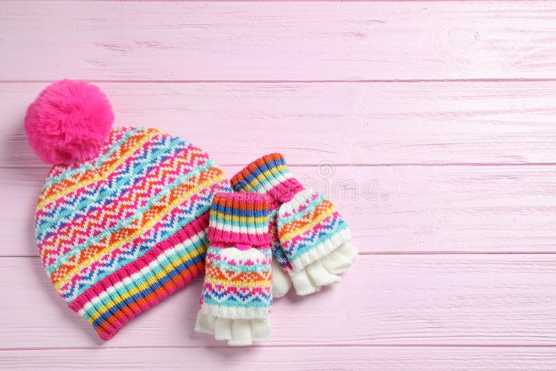 Warm knitted hat and mittens on pink wooden background. Space for text. Warm knitted hat and mittens on pink wooden background, flat lay. Space for text royalty free stock photos