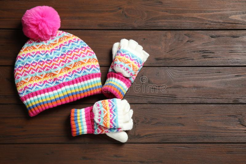 Warm knitted hat and mittens on wooden background. Space for text. Warm knitted hat and mittens on wooden background, flat lay. Space for text royalty free stock photos