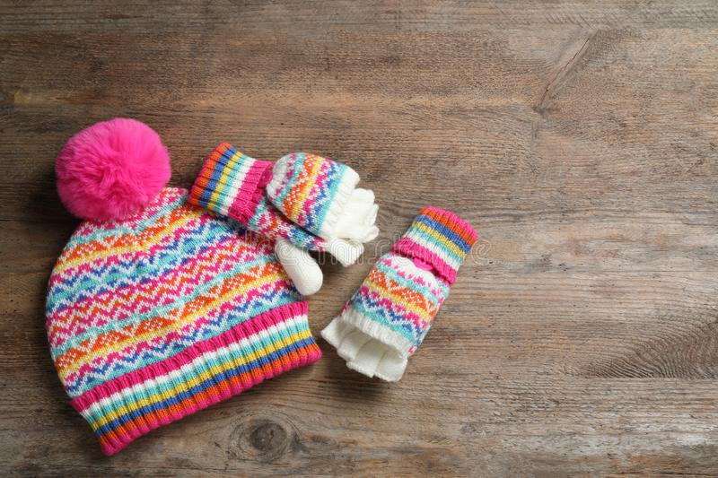 Warm knitted hat and mittens on wooden background. Space for text. Warm knitted hat and mittens on wooden background, flat lay. Space for text royalty free stock photo