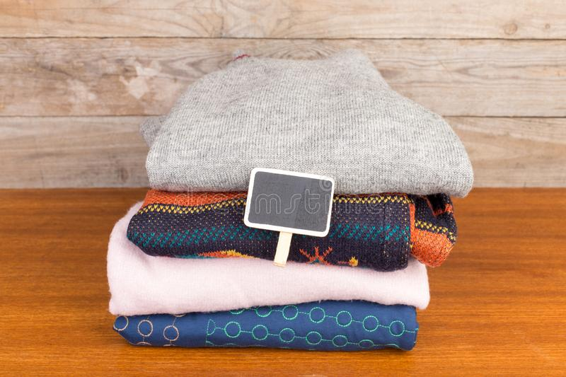 Warm knitted sweaters on blank wooden background. Set of winter pullovers and blank signboard royalty free stock images