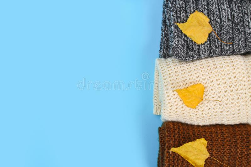 Warm knitted sweaters. Pile of knitted clothes on blue background, sweaters, knitwear, space for text, Autumn winter concept. Top. View royalty free stock photos