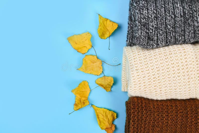 Warm knitted sweaters. Pile of knitted clothes on blue background, sweaters, knitwear, space for text, Autumn winter concept. Top. View stock photos
