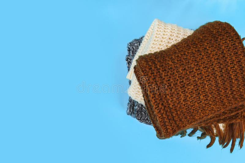 Warm knitted sweaters. Pile of knitted clothes on blue background, sweaters, knitwear, space for text, Autumn winter concept. Top. View stock images