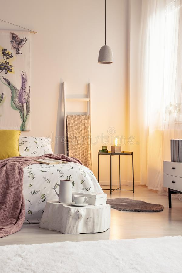 Warm lamp light in a soft colors bedroom interior with a bed dressed in bedding, cushions and blanket. Painted material art on the stock photo