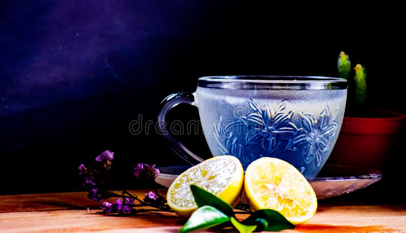 Blue Lemon soda, soft drinks served in beautiful crystal cup with small dish on wooden table with sunshine morning. Warm Lemon soda,healthy drinks served in stock photography