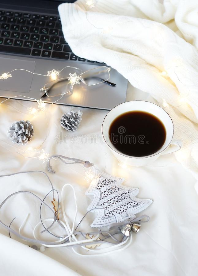Warm lifestyle autumn winter composition. Koffee, laptop, knitted sweater , glasses and Christmas decor. home workspace in bed concept.warm lifestyle autumn stock image
