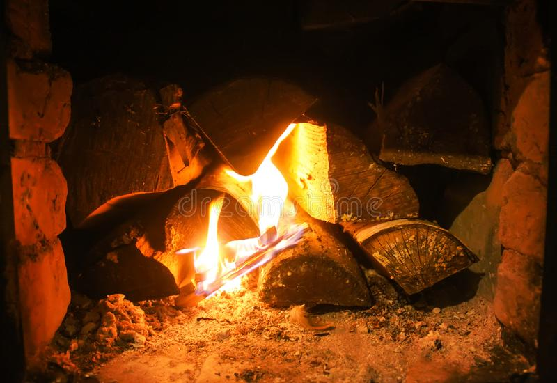 Warm light of a burning fire in a fireplace in old Russian stove. Flame and firewood background. Detail of interior. Warm light of a burning bright fire in a royalty free stock photos