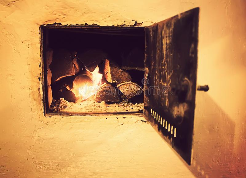 Warm light of a burning fire in a fireplace in old Russian stove. Flame and firewood background. Detail of interior. Warm light of a burning bright fire in a royalty free stock image