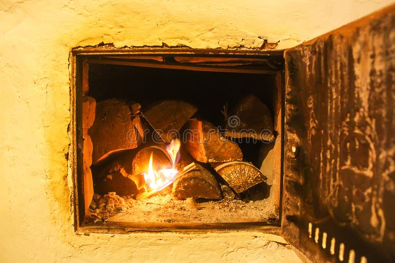 Warm light of a burning fire in a fireplace in old Russian stove. Flame and firewood background. Detail of interior. Warm light of a burning bright fire in a stock photo