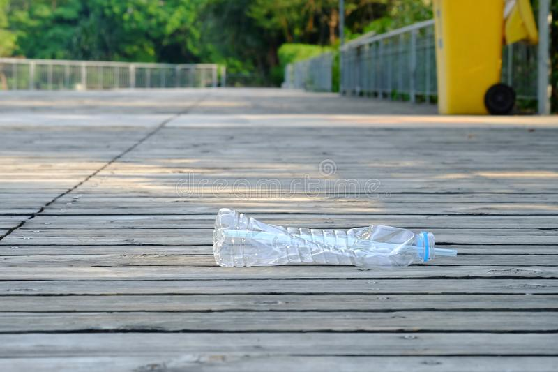 A plastic bottle of drinking water with a straw littering on old wood ground floor stock photo
