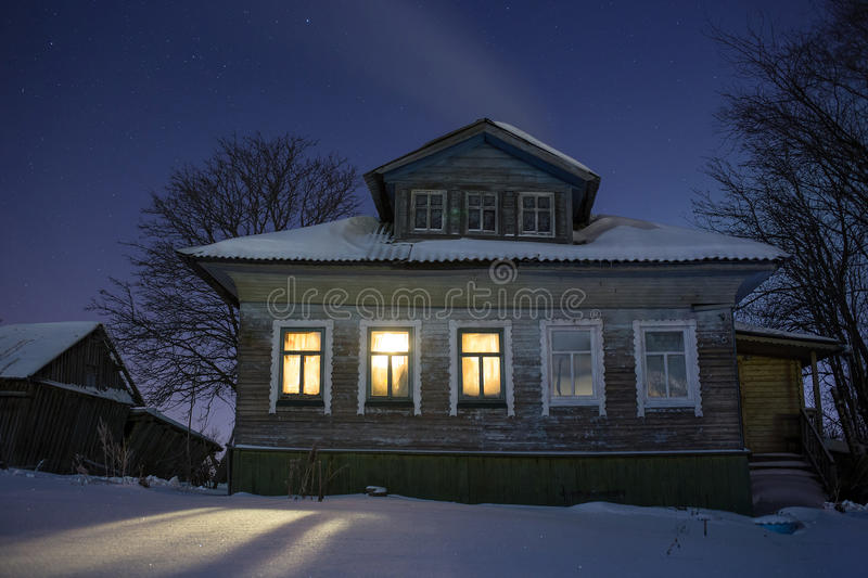 Warm light from windows cozy old russian village house in the bitter cold. Winter night landscape with snow, stars royalty free stock image