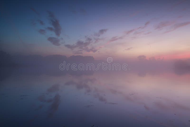 Warm misty sunrise in summer over river