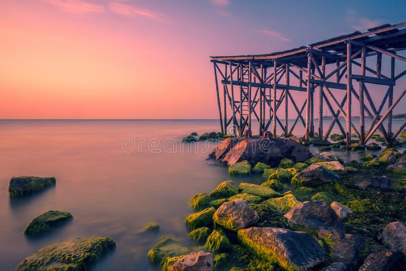Warm morning on the seaside at sunrise with a pier on the shore and beautiful rocks covered with algae royalty free stock photos