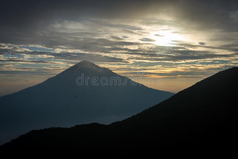 Warm morning sunrise on Tebing Soni with view of mount Cikuray. Beautiful landscape of mount Papandayan. Papandayan Mountain is. One of the favorite place to royalty free stock images