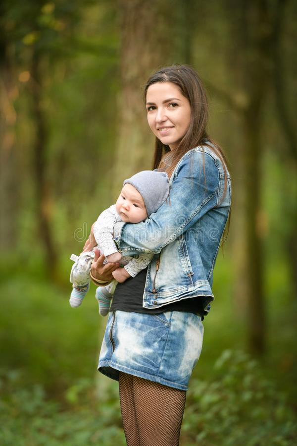 Warm mother`s hands. Happy mother walks with her baby in her arms. Mom talks to a happy child, the child sits in her mother s arm. S royalty free stock photography