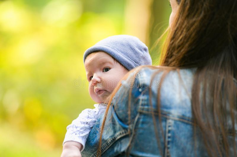 Warm mother`s hands. Happy mother walks with her baby in her arms. Mom talks to a happy child, the child sits in her mother s arm. S royalty free stock images