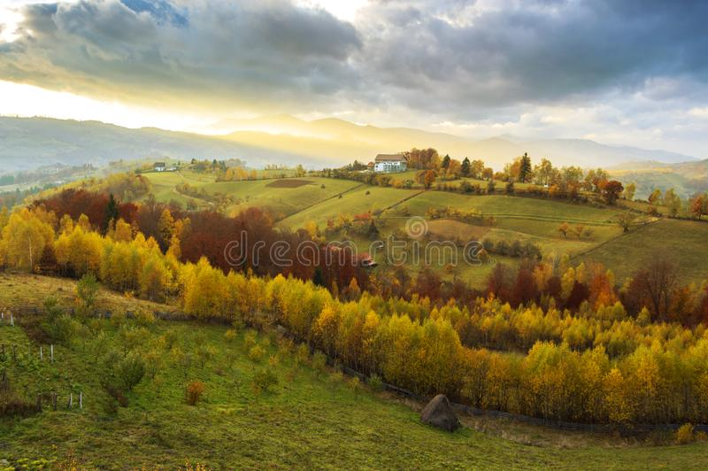 Warm October evening in Transylvania. Magic autumn sunset landscape. Hills and mountains bathed in warm sunset light in Poiana Marului, Romania. Magic autumn royalty free stock image