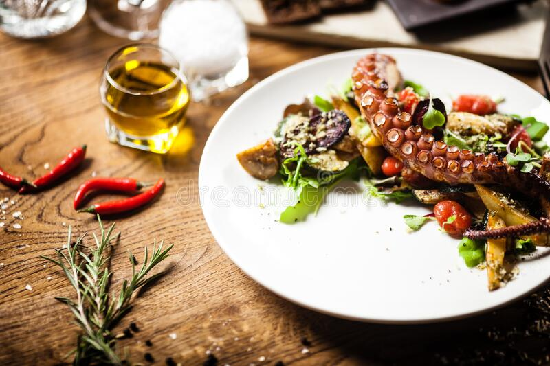 Octopus salad served on a plate in restaurant royalty free stock photography