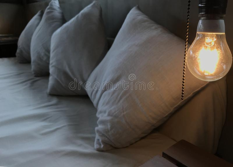 The warm orange glowing incandescent light bulb on the head of the white wooden bed. Loft Interior Design, comfortable and relax. Ing furniture concept stock photo