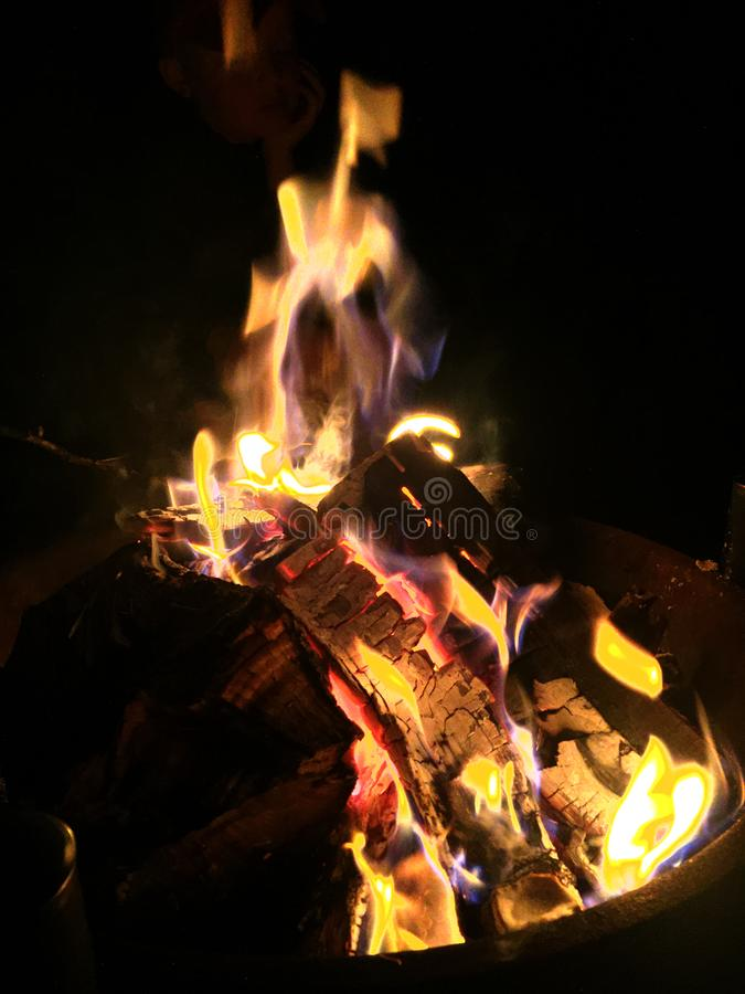 Warm outdoor fire burning orange at night with glowing logs royalty free stock images