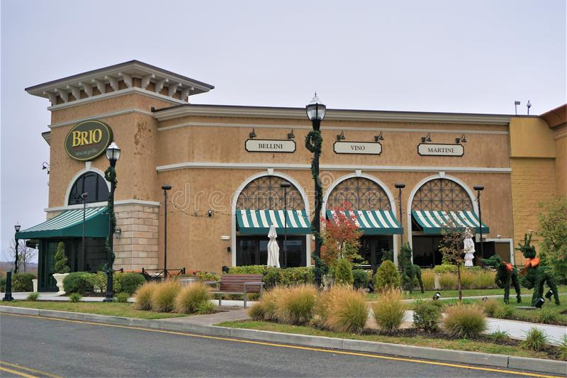 Brio restaurant at Danbury Mall Connecticut during holidays. Warm and overcast winter day allows the ornamental grasses, wreathed lawn animals and sidewalks to royalty free stock photo