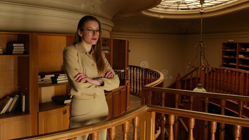 On A Warm Pale Light In The Old Library Beautiful Young Woman In Suit And  Glasses Choose A Book To Read Stock Footage - Video of campus 4995fcacf