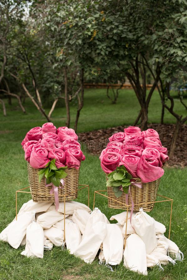 Warm pink blankets rolled up in the form of roses in a large basket for guests at an outdoor wedding party. Individual dance white royalty free stock image