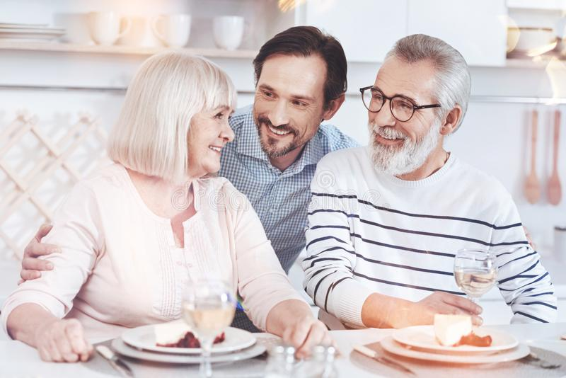 Cheerful adult son embracing his positive elderly parents stock images